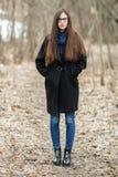 Ung härlig flicka i svarta exponeringsglas för en lagblåtthalsduk som går i hösten/våren Forest Park En elegant brunettflicka med Royaltyfria Bilder