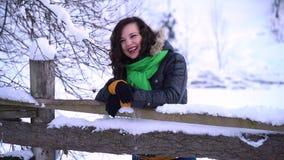 Ung härlig flicka i vinterskogen som ser kameran och att skratta Flickan står nära ett trästaket Hon är stock video