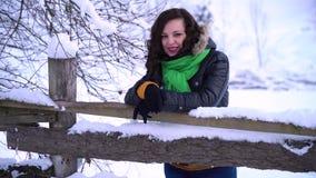 Ung härlig flicka i vinterskogen som ser kameran och att skratta Flickan står nära ett trästaket Hon är lager videofilmer