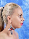Ung härlig flicka med arga örhängen på abstrakt bakgrund Arkivbild