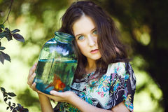 Ung härlig flicka med den guld- fisken Fotografering för Bildbyråer