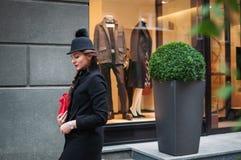 Ung härlig flicka med den röda påsen och att bära en svart hatt och en leath Royaltyfri Foto
