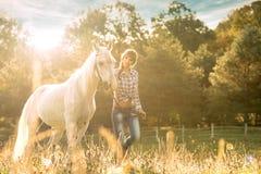 Ung härlig flicka med en häst på det torra fältet Fotografering för Bildbyråer