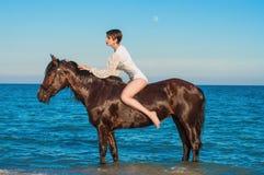 Ung härlig flicka med en häst på stranden Royaltyfria Bilder