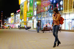 Ung härlig flicka med en röd ryggsäck, nära den shoppa cenen royaltyfri fotografi