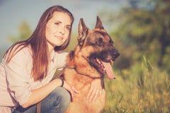 Ung härlig flicka med en tysk herde som spelar på gräsmattan Royaltyfria Bilder