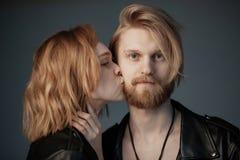 Ung härlig flicka med lockigt hår som kysser hennes skäggiga pojkvän arkivbilder
