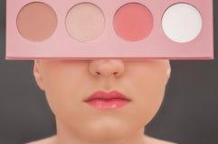 Ung härlig flicka med rosa läppstift som döljer hennes framsida bak s arkivbilder