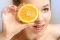 Ung härlig flicka med skivan av apelsinen Arkivbilder