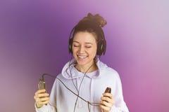 Ung härlig flicka med vita tänder som lyssnar till musik på den bärande hörlurar för telefon i en tröja på en lila Arkivfoton