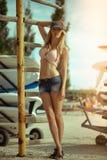 Ung härlig flicka på gamla surfa och vindsurfa stationsställningar nära surfingbrädorna som installeras på de utomhus- kuggarna arkivfoton