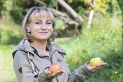 Ung härlig flicka rymma mogna nya äpplen med ett gulligt leende Royaltyfri Fotografi