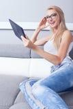 Ung härlig flicka som använder minnestavlan Royaltyfria Bilder