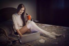Ung härlig flicka som arbetar med hennes hemmastadda bärbar dator royaltyfria bilder