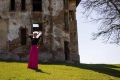 Ung härlig flicka som framme poserar av en gammal herrgård Arkivbilder