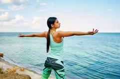 Ung härlig flicka som gör övningar på stranden Arkivbild