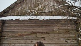 Ung härlig flicka som har rolig kasta snö som in poserar på kamera i vinterkläder på bakgrund av trähuset stock video