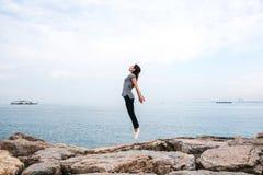 Ung härlig flicka som hoppar beskriva uppåt ett flyg mot bakgrunden av havet och himlen Begreppet av royaltyfri bild