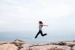 Ung härlig flicka som hoppar beskriva uppåt ett flyg mot bakgrunden av havet och himlen Begreppet av fotografering för bildbyråer