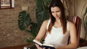 Ung härlig flicka som läser ett boksammanträde i en stol Attraktiv kvinna som ler, medan läsa en bok positiva sinnesrörelser stock video