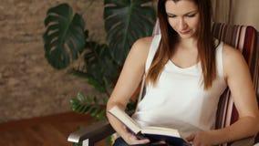 Ung härlig flicka som läser ett boksammanträde i en stol En attraktiv kvinna skrattar, medan läsa en bok close upp stock video