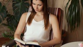 Ung härlig flicka som läser ett boksammanträde i en stol En kvinna i hennes extra- tid läser uppmärksamt en bok close upp lager videofilmer