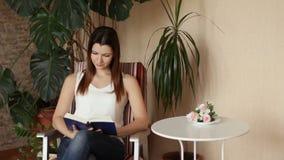 Ung härlig flicka som läser ett boksammanträde i en stol Kvinna som ler läsa en favorit- bok positiva sinnesrörelser lager videofilmer
