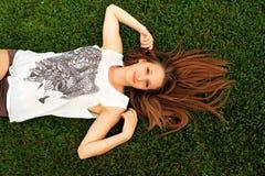 Ung härlig flicka som ligger på en grön gräsmatta Royaltyfri Foto
