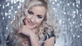 Ung härlig flicka som poserar i elegant klänning över skinande bakgrund stock video
