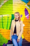 Ung härlig flicka som poserar på väggbakgrund med grafitti Royaltyfria Bilder