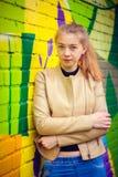 Ung härlig flicka som poserar på väggbakgrund med grafitti Royaltyfri Bild