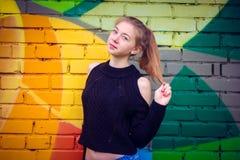 Ung härlig flicka som poserar på väggbakgrund med grafitti Fotografering för Bildbyråer