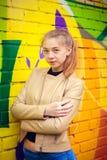 Ung härlig flicka som poserar på väggbakgrund med grafitti Arkivfoto