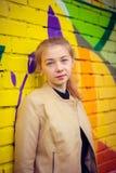 Ung härlig flicka som poserar på väggbakgrund med grafitti Royaltyfri Foto