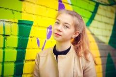 Ung härlig flicka som poserar på väggbakgrund med grafitti Royaltyfri Fotografi