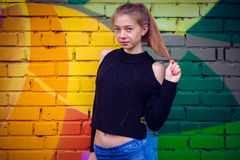 Ung härlig flicka som poserar på väggbakgrund med grafitti Arkivbild