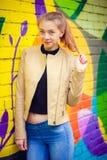 Ung härlig flicka som poserar på väggbakgrund med grafitti Arkivbilder