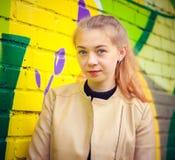 Ung härlig flicka som poserar på väggbakgrund med grafitti Arkivfoton