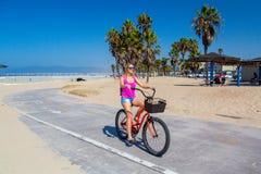 Ung härlig flicka som rider en cykel ner den Venedig stranden arkivfoto