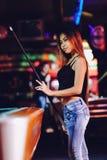 Ung härlig flicka som spelar billiard i en klubba Royaltyfria Bilder