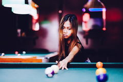 Ung härlig flicka som spelar billiard i en klubba Arkivbilder