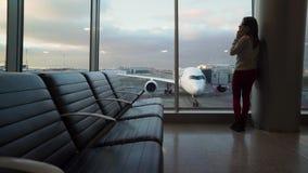 Ung härlig flicka som talar på telefonen i flygplatsterminal mot bakgrunden av ett flygplan stock video