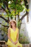 Ung härlig flicka som väljer nya mogna limefrukter eller citroner i solig trädgård i Italien Arkivbild