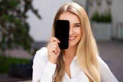 Ung härlig flicka som visar din smartphoneskärm royaltyfri fotografi