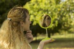 Ung härlig flickablick in i spegeln i parkera Mjuk och suddighetsbefruktning Arkivfoton