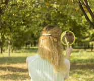 Ung härlig flickablick in i spegeln i parkera Mjuk och suddighetsbefruktning Arkivbild