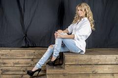 Ung härlig flickablondin i en vit skjorta och jeans med mellanrum fotografering för bildbyråer