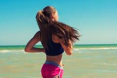 Ung härlig flickaidrottsman nen som spelar sportar på stranden Arkivfoton