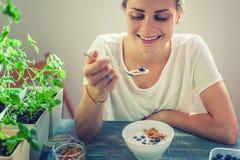 Ung härlig flickakvinna som äter yoghurt med flingor och bär royaltyfri fotografi