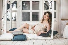 Ung härlig gravid kvinna hemma i sovrummet mot th royaltyfri fotografi